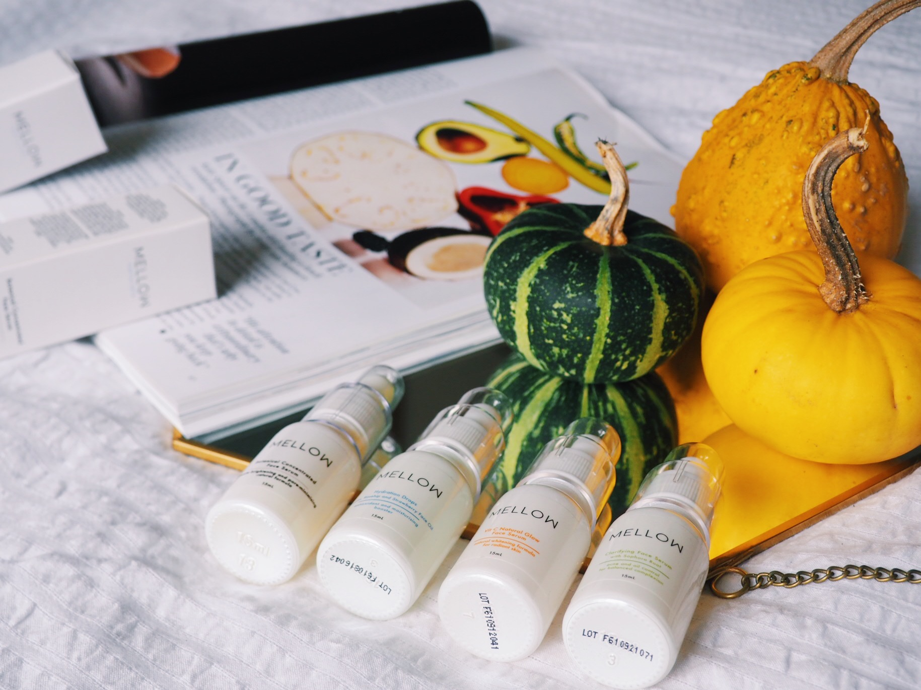 A collection of serums from Mellow Naturals Skincare, photographed alongside Vogue magazine and some fancy squash in an Autumnal lifestyle image